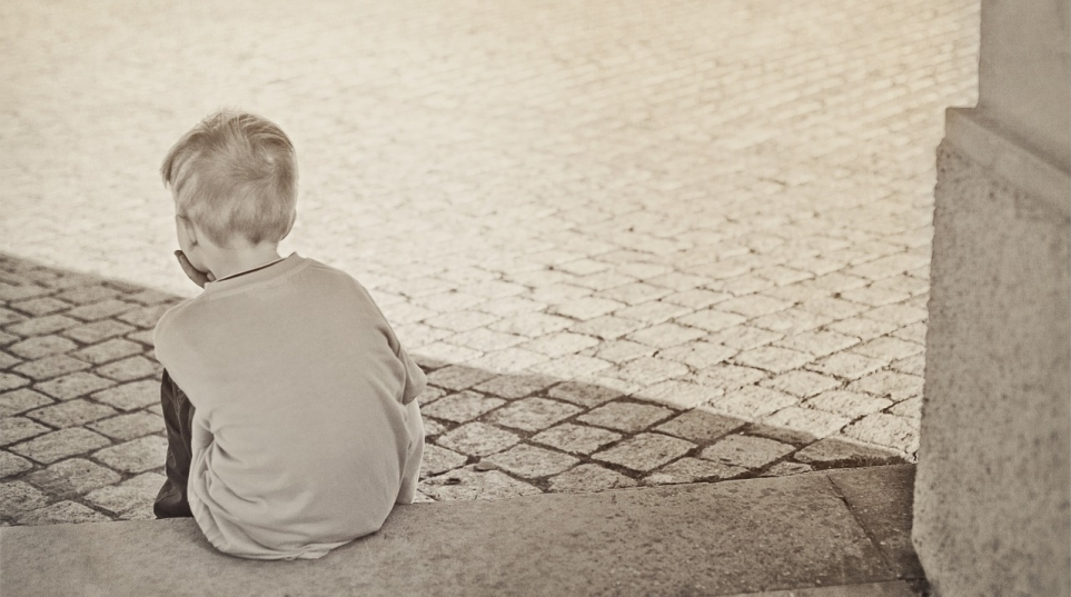 black and white image of disappointed little boy sitting on steps
