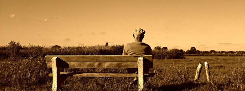 Sepia image of an old man sittingon a bench and looking over the countryside